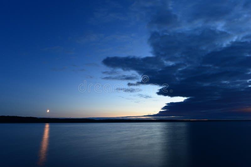 Het duidelijke maanlicht van de nachthemel op de oppervlakte van het meerwater stock foto