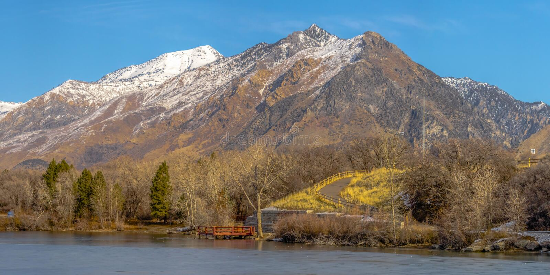 Het duidelijke Panorama Ijzige meer en de opvallende sneeuw dekten berg tegen trillende blauwe hemel in de winter af royalty-vrije stock afbeeldingen