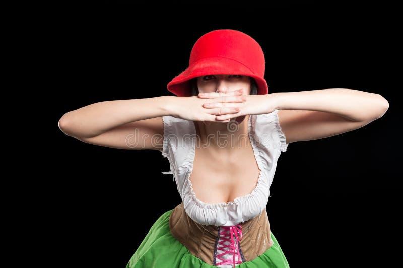 Het Duitse mooie meisje met rode hoed behandelt mond stock fotografie