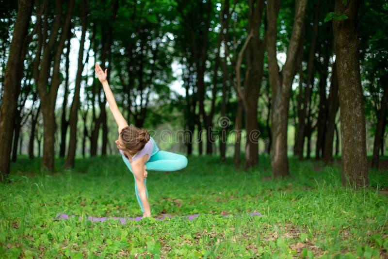 Het dunne donkerbruine meisje speelt sporten en voert mooie en verfijnde yoga uit stelt in een de zomerpark Groen weelderig bos o stock afbeelding