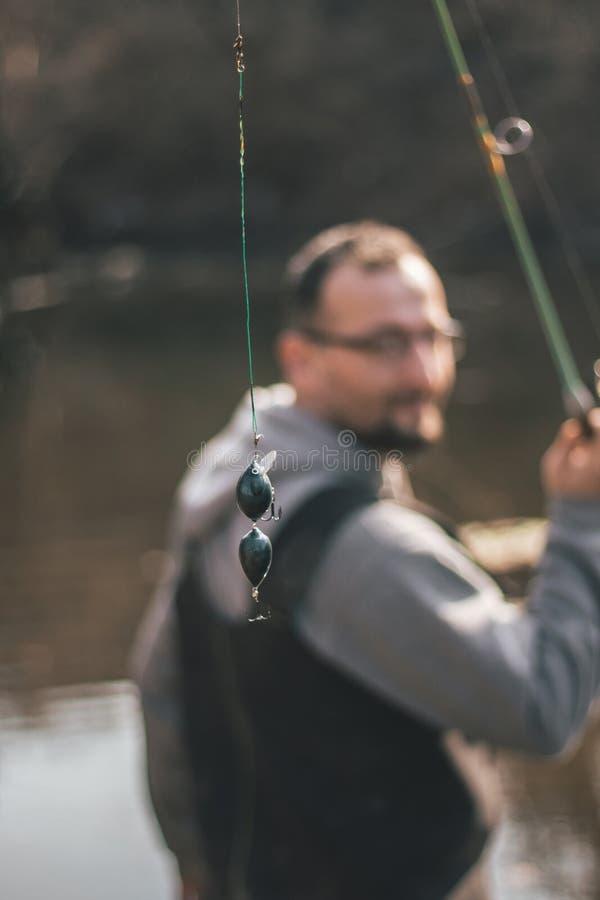 Het duwende aas van de visserscontrole op de vislijn royalty-vrije stock fotografie