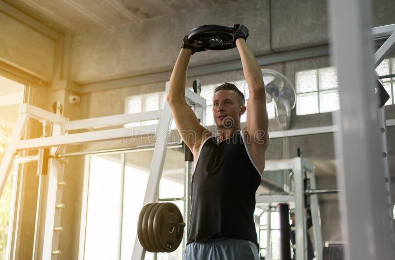 Het dwars geschikte lichaam en de spier opheffende gewichtsbar in de gymnastiek, Sportmens het doen oefenen opleiding uit stock foto's