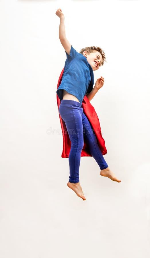 Het dynamische geïsoleerde super heldenjongen hoog springen, vliegend over wit stock afbeeldingen