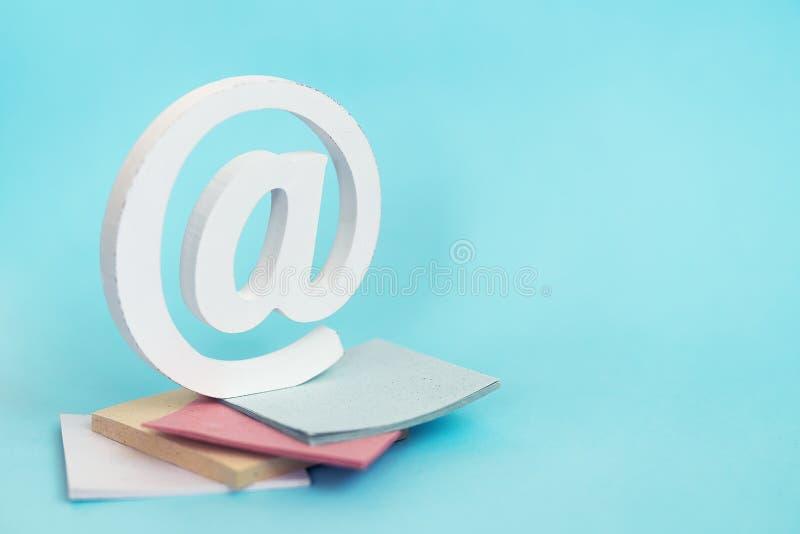 Het e-mailteken op een stapel stickers op blauw Concept als achtergrond voor e-mail, mededeling of contacteert ons stock afbeeldingen