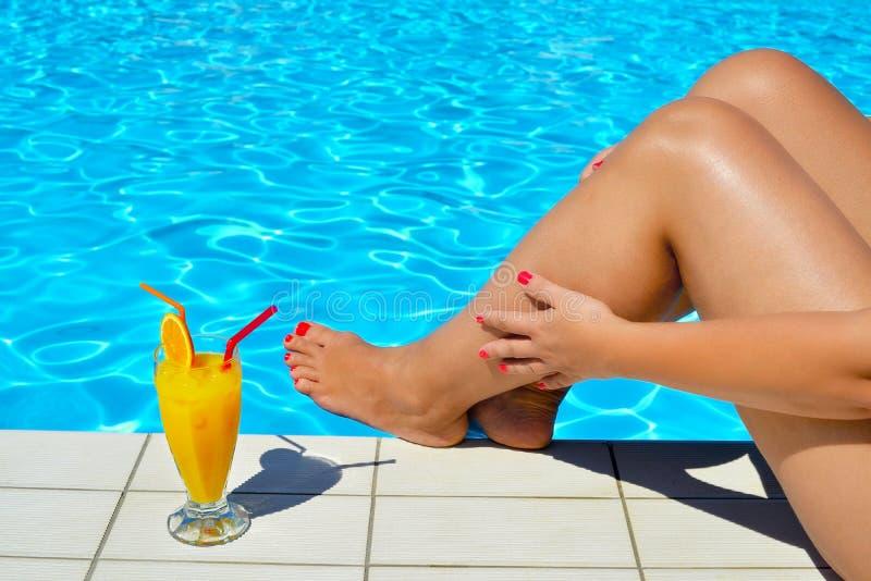Het echte vrouwelijke schoonheid ontspannen bij zwembad stock foto's