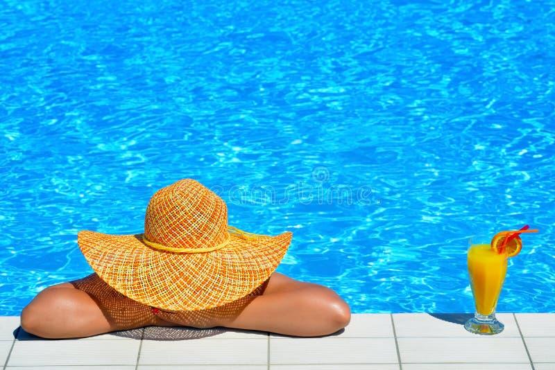 Het echte vrouwelijke schoonheid ontspannen bij zwembad stock foto