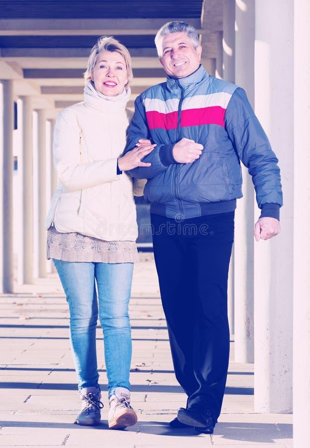 Het echtpaar gaat voor gang tussen concrete pijlers royalty-vrije stock foto's
