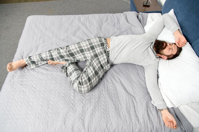 Het is een lange nacht geweest rijp mannetje met baard in pyjama op bed in slaap en wakker energie en vermoeidheid Gebaarde mens royalty-vrije stock foto