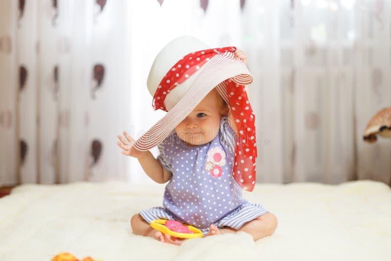 Het een weinig grappige Kaukasische meisje een kind zit thuis op de vloer op een licht tapijt Op zijn hoofd is een grote de zomer royalty-vrije stock afbeelding