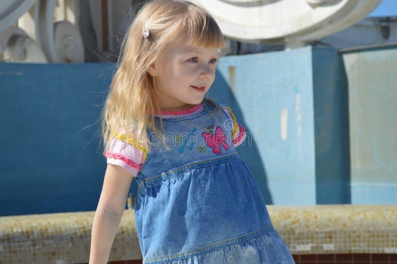 Het een weinig mooie meisje glimlacht en onderzoekt de afstand royalty-vrije stock foto's