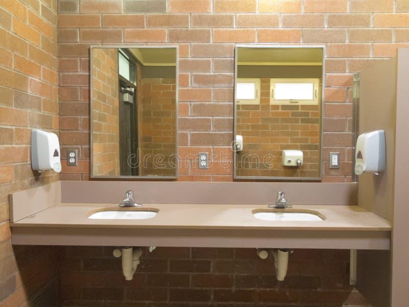 Het eenvoudige schone openbare toilet daalt spiegels stock foto's