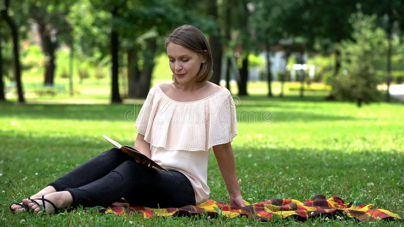 Het eenzame boek van de damelezing in park, uiteinden voor vrouwen hoe te om gevende echtgenoot te vinden stock fotografie
