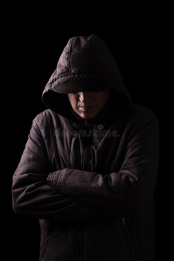 Het eenzame, gedeprimeerde en breekbare mensen verbergende gezicht, bewapent gekruist en zich bevindt in de duisternis royalty-vrije stock fotografie