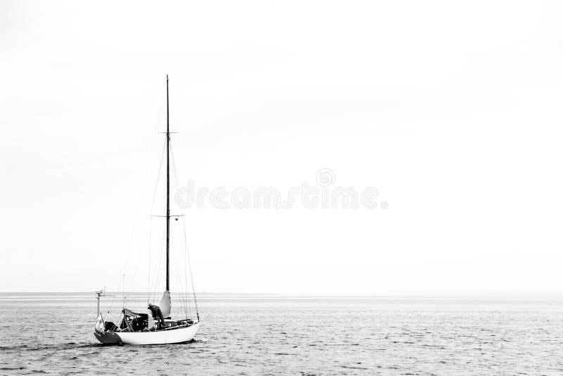 Het eenzame kleine jacht gaat naar de open zee stock fotografie