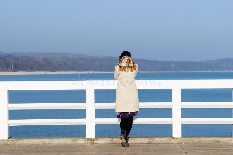 Het eenzame mooie droevige meisje bevindt zich op de pijler op een zonnige warme de herfstavond bij het overzees royalty-vrije stock afbeelding