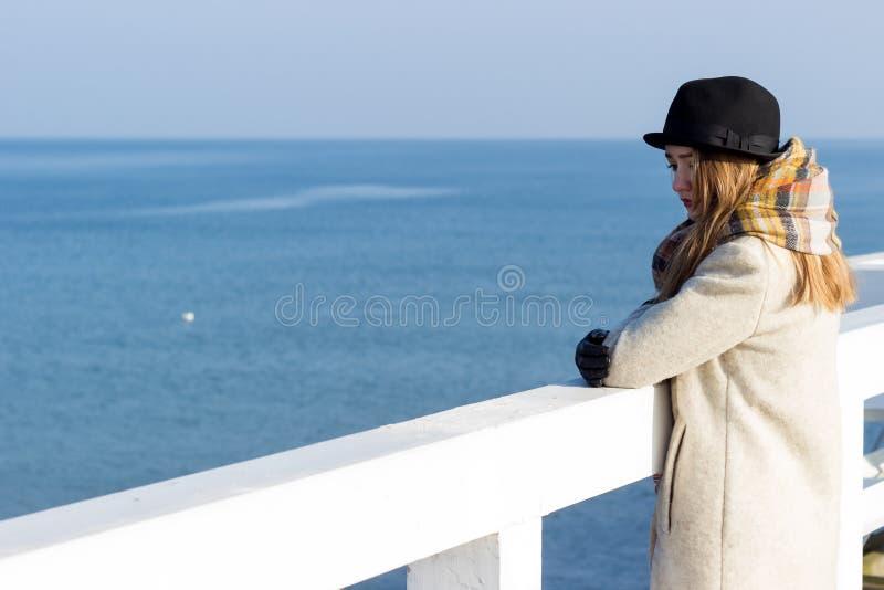 Het eenzame mooie droevige meisje bevindt zich op de pijler op een zonnige warme de herfstavond bij het overzees stock afbeeldingen