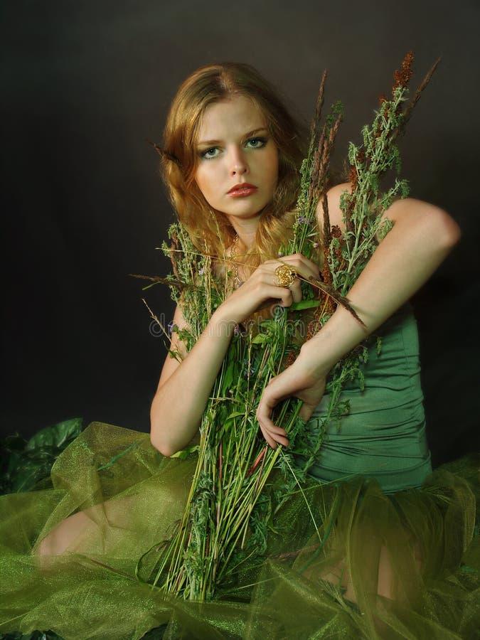 Het eenzame mooie meisje met een gras stock afbeeldingen
