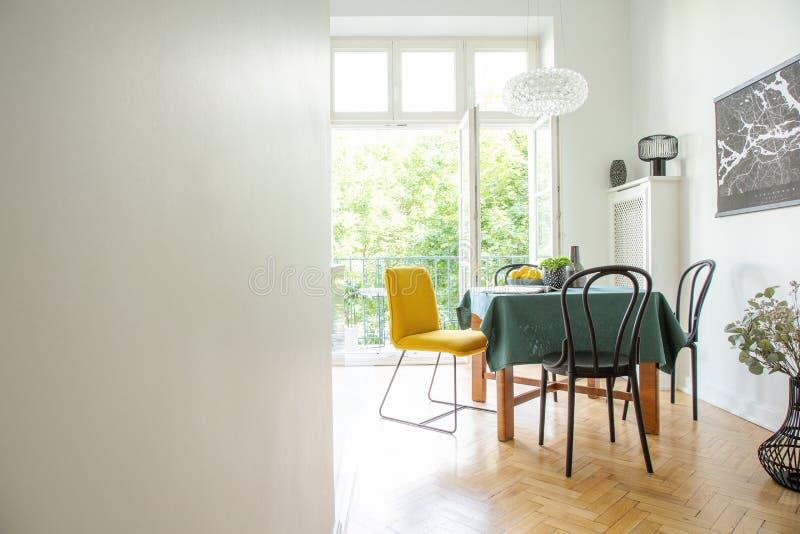 Het eetkamerbinnenland met houten meubilair, witte muren, kopieert ruimte en brede open glasdeur aan balkon royalty-vrije stock fotografie