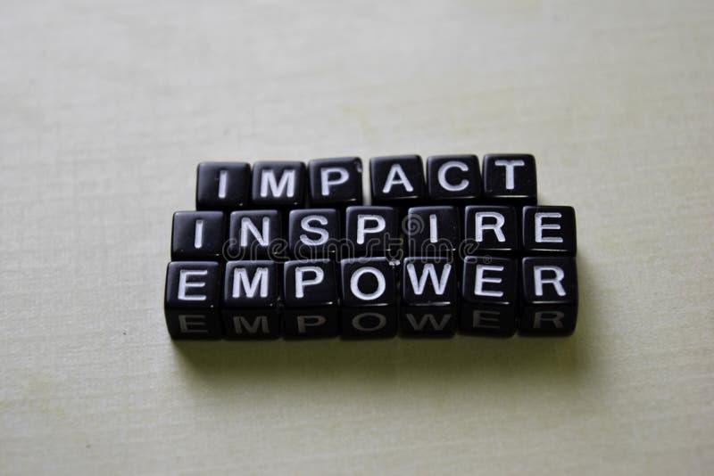 Het effect - inspireer - machtigt op houten blokken Bedrijfs en inspiratieconcept stock afbeelding