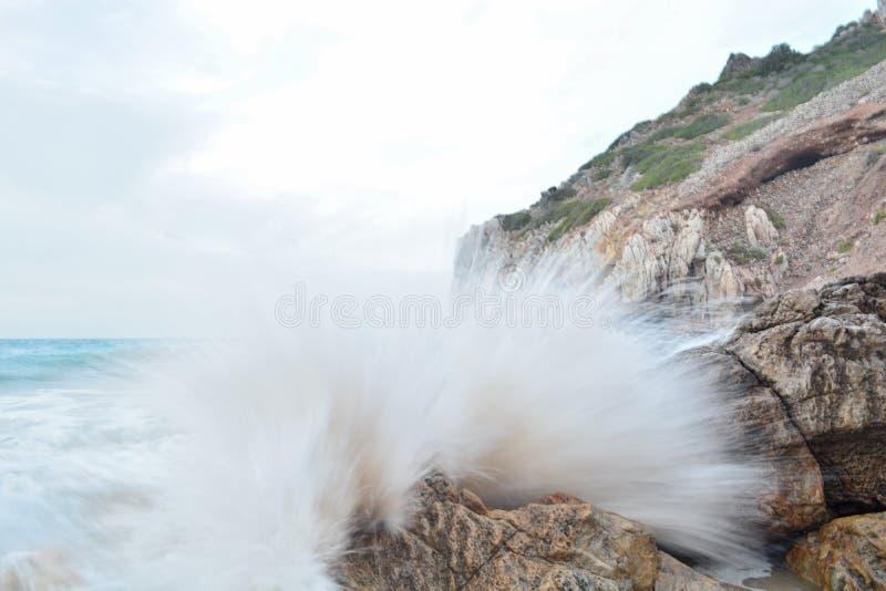 Het effect van de golfneerstorting op de rotsen royalty-vrije stock afbeelding