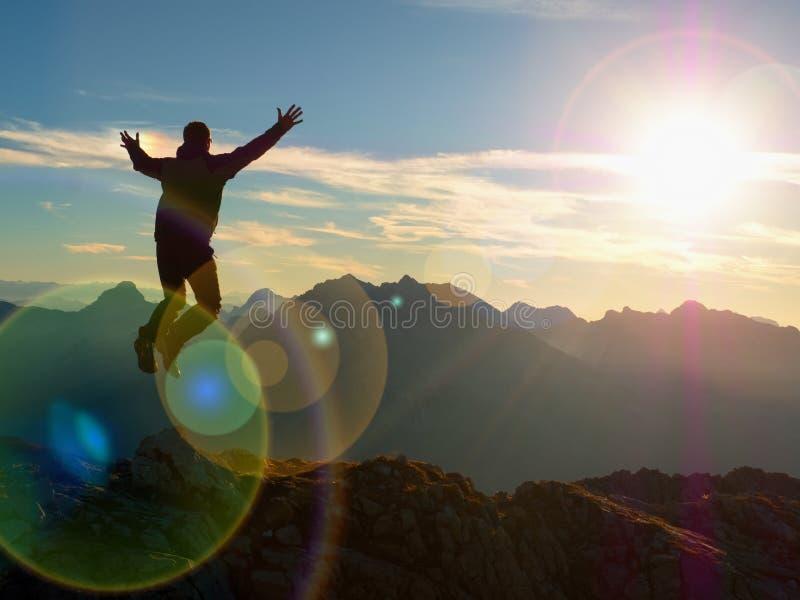 Het effect van de lensgloed Boog lichte cirkels Gekke wandelaar die bij piek van berg springen royalty-vrije stock afbeeldingen