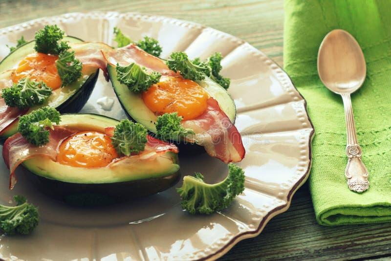 Het Eiboten van de ontbijtavocado met knapperig bacon, boerenkoolkool stock afbeelding
