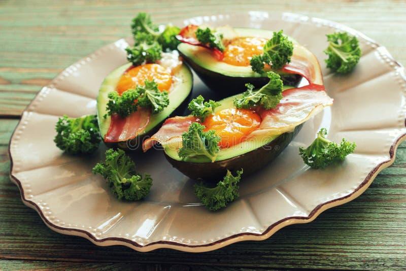 Het Eiboten van de ontbijtavocado met knapperig bacon, boerenkoolkool royalty-vrije stock afbeelding
