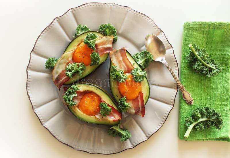 Het Eiboten van de ontbijtavocado met knapperig bacon, boerenkoolkool op witte achtergrond stock fotografie