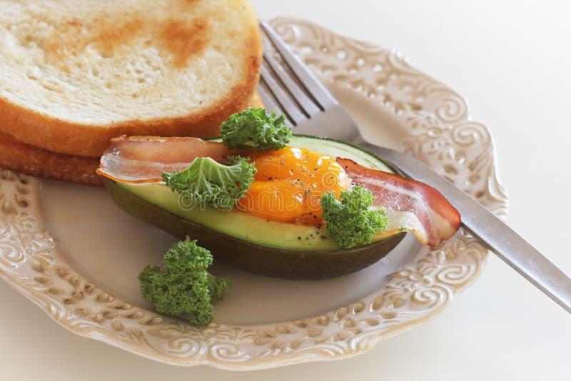 Het Eiboten van de ontbijtavocado met knapperig bacon, boerenkoolkool op witte achtergrond royalty-vrije stock foto's