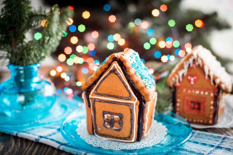 Het eigengemaakte die Huis van de Kerstmispeperkoek op een lijst wordt getoond Kerstboomlichten op de achtergrond royalty-vrije stock afbeelding