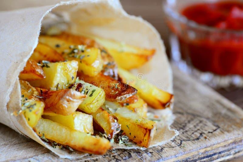 Het eigengemaakte gebraden aardappelsontbijt sneed gebraden aardappels in document en houten raad close-up royalty-vrije stock afbeelding