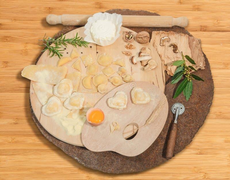 Het eigengemaakte Italiaanse hart vormde ravioli met verse kaas, bloem, ei, okkernoten en aromatische die kruiden op een rustiek  royalty-vrije stock foto's