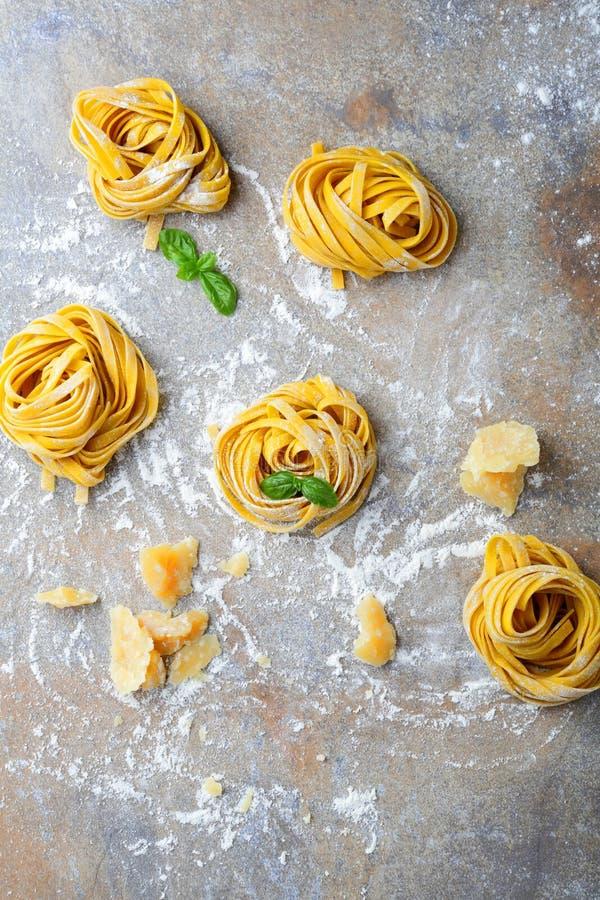 Het eigengemaakte nest, de parmezaanse kaas en het basilicum van tagliatelledeegwaren stock foto