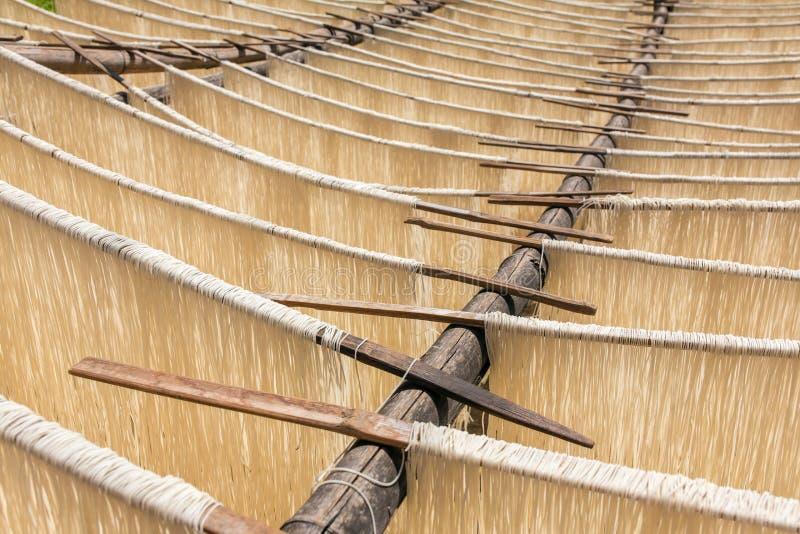Het eigengemaakte rijstdeegwaren drogen op zon stock afbeeldingen