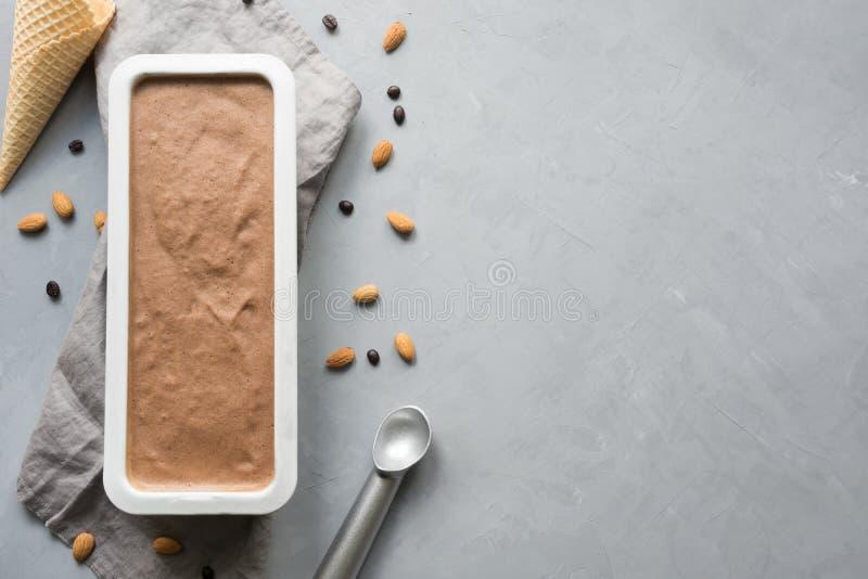 Het eigengemaakte roomijs van de banaanchocolade in container met koffiebonen op grijs Ruimte voor tekst Hoogste mening royalty-vrije stock afbeeldingen