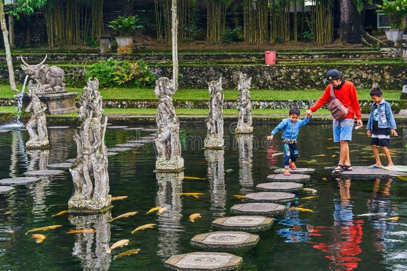 HET EILAND VAN BALI, INDONESIË - DECEMBER 17, 2017: De familie loopt I stock fotografie