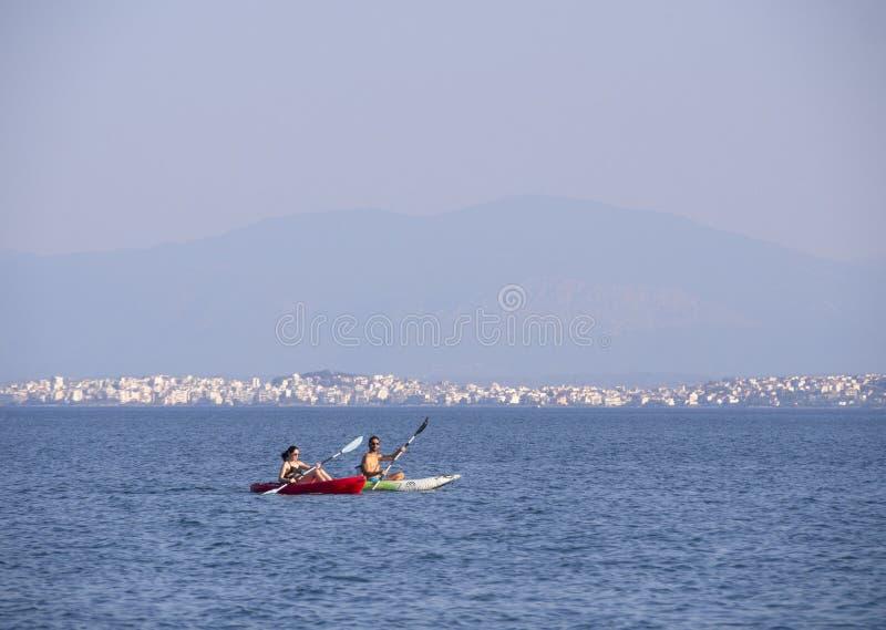Het eiland van Evvoia, Griekenland Juli 2019: Man en vrouwen het kayaking in het Egeïsche overzees op een Grieks eiland op een de royalty-vrije stock fotografie