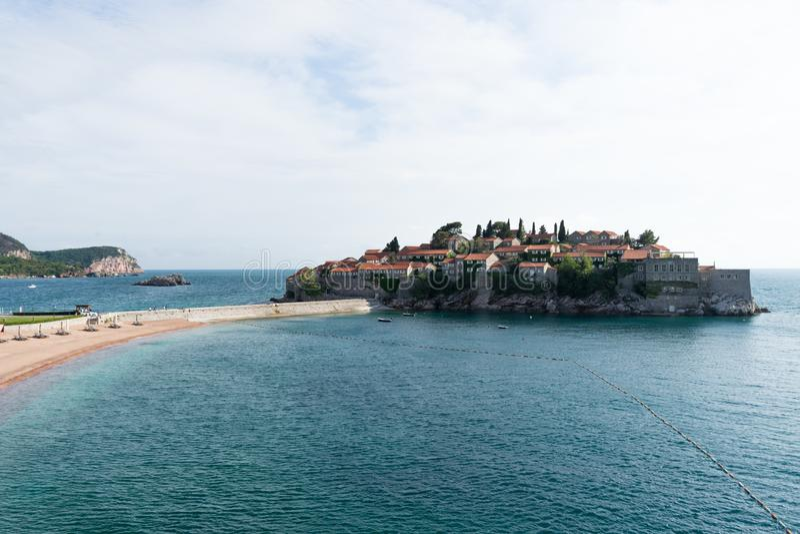 Het eiland van Svetistefan in Budva in een mooie de zomerdag, Montenegro Het strand van het luxezand met houten chaise-longuestoe royalty-vrije stock foto