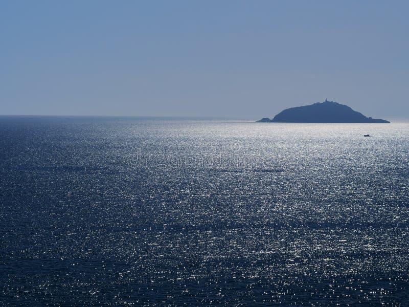Het eiland van Tino dichtbij Portovenere, Ligurië Zonlichtfonkelingen op het zilveren overzees Idyllisch, met kleine boot stock afbeeldingen