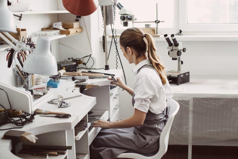 Het eind van de werkdag Zijaanzicht van jonge vrouwelijke juwelierzitting op haar juwelenworkshop en het schoonmaken van haar wer royalty-vrije stock foto