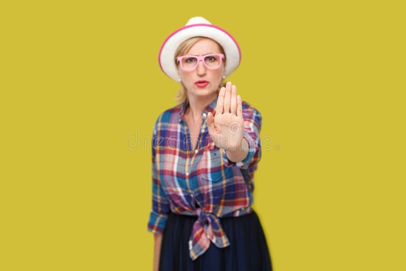 Het einde of wacht Portret van boze of doen schrikken moderne modieuze rijpe vrouw in toevallige stijl met hoed en oogglazen die  royalty-vrije stock afbeelding