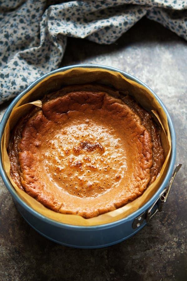 Het eindigen vers bakte karamelkaastaart in cakevorm op een donkere achtergrond stock fotografie