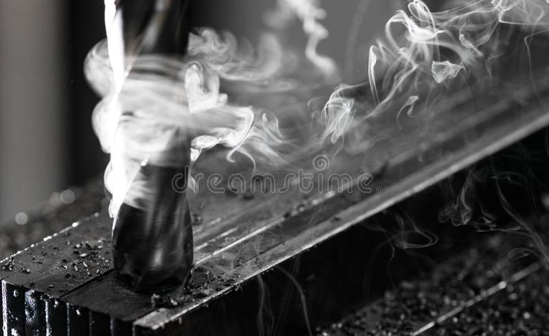 Het eindmolen die van Bridgeport CNC een stapel van staalplaat beëindigen met metaal het indienen spaanders en zeer zware rook stock foto's