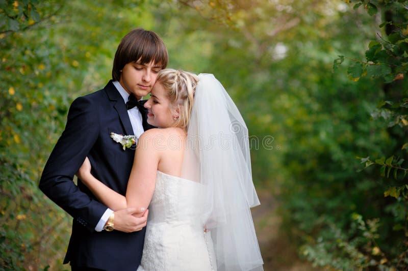 Het elegante bruid en bruidegom stellen samen in openlucht op een huwelijk DA stock fotografie
