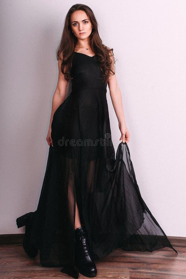 Het elegante donkerbruine dame stellen in zwarte avondjurk Het schot van de studio stock foto