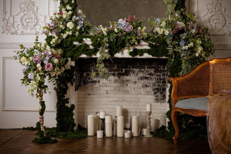 Het elegante grijze hoogtepunt van de baksteenopen haard van bloemen en kaarsen Elegante ruimte Huwelijk verfraaid gebied Uitstek stock fotografie