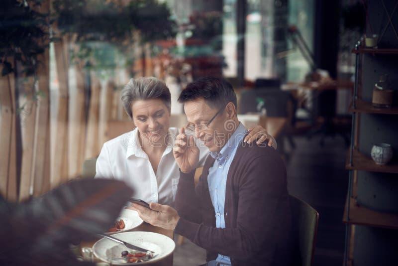 Het elegante paar kijkt met rente in mobiele telefoon stock foto