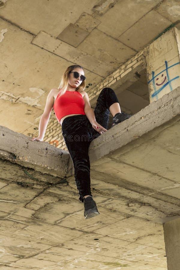 het elegante vrouw stellen bij verlaten bouwwerf stock fotografie
