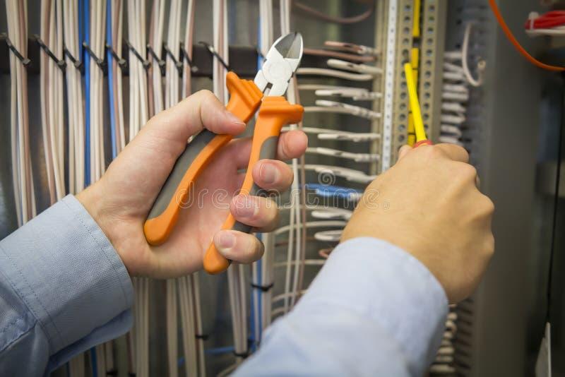 Het elektrische installatiewerk Schroevedraaier en buigtang in handen van een elektricien op achtergrond van elektrisch kabinet royalty-vrije stock fotografie
