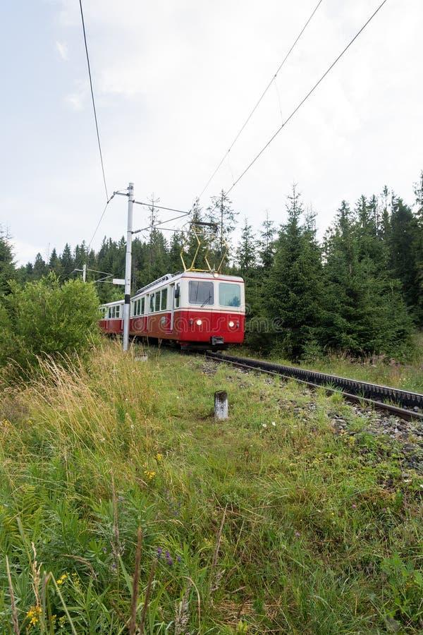 Het elektrische trein lopen op sporen met toestel, Hoge Tatras, Slowakije stock foto